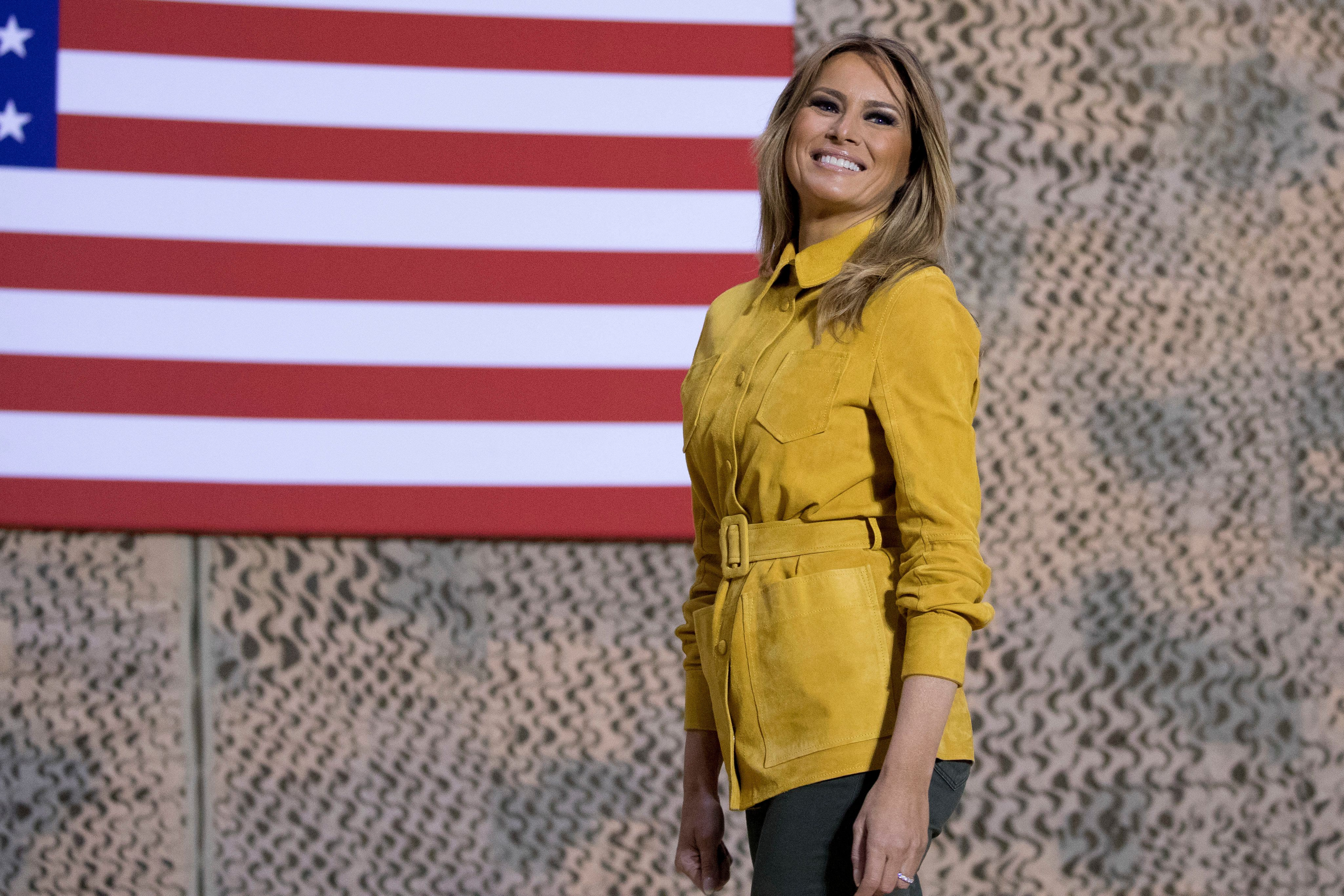 First lady Melania Trump smiles as she steps away from the podium after speaking alongside President Donald Trump at a hangar rally at Al Asad Air Base, Iraq, Wednesday, Dec. 26, 2018. In a surprise trip to Iraq, President Donald Trump on Wednesday defended his decision to withdraw U.S. forces from Syria where they have been helping battle Islamic State militants. (AP Photo/Andrew Harnik)