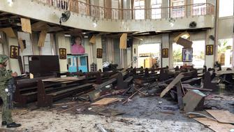 "In this photo provided by WESMINCOM Armed Forces of the Philippines, a soldier views the site inside a Roman Catholic cathedral in Jolo, the capital of Sulu province in the southern Philippines after two bombs exploded Sunday, Jan. 27, 2019. The Philippine government says it will ""pursue to the ends of the earth the ruthless perpetrators"" behind bomb attacks that killed over a dozen people and wounded many more during a Sunday Mass at a cathedral on the restive southern island. (WESMINCOM Armed Forces of the Philippines Via AP)"