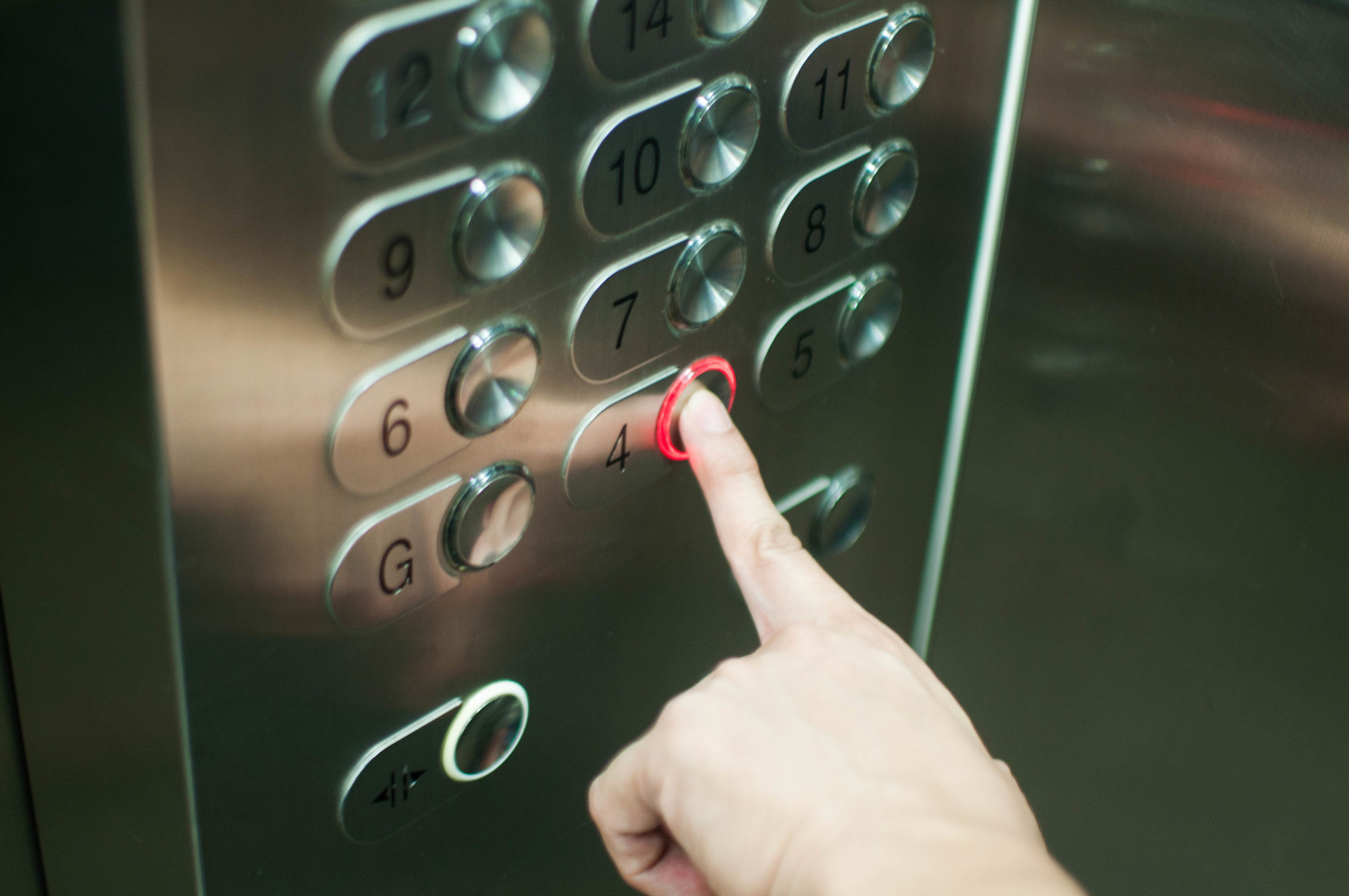 A person is pressing the elevator button with left hand