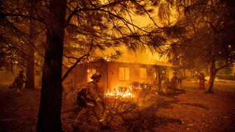 FILE - In this Friday, Nov. 9, 2018, file photo firefighters work to keep flames from spreading through the Shadowbrook apartment complex as a wildfire burns through Paradise, Calif. Authorities say the fire is 95 percent contained Thursday, Nov. 22. The blaze that started Nov. 8 leveled Paradise, killing multiple people and destroyed more than 13,000 homes. (AP Photo/Noah Berger, File)