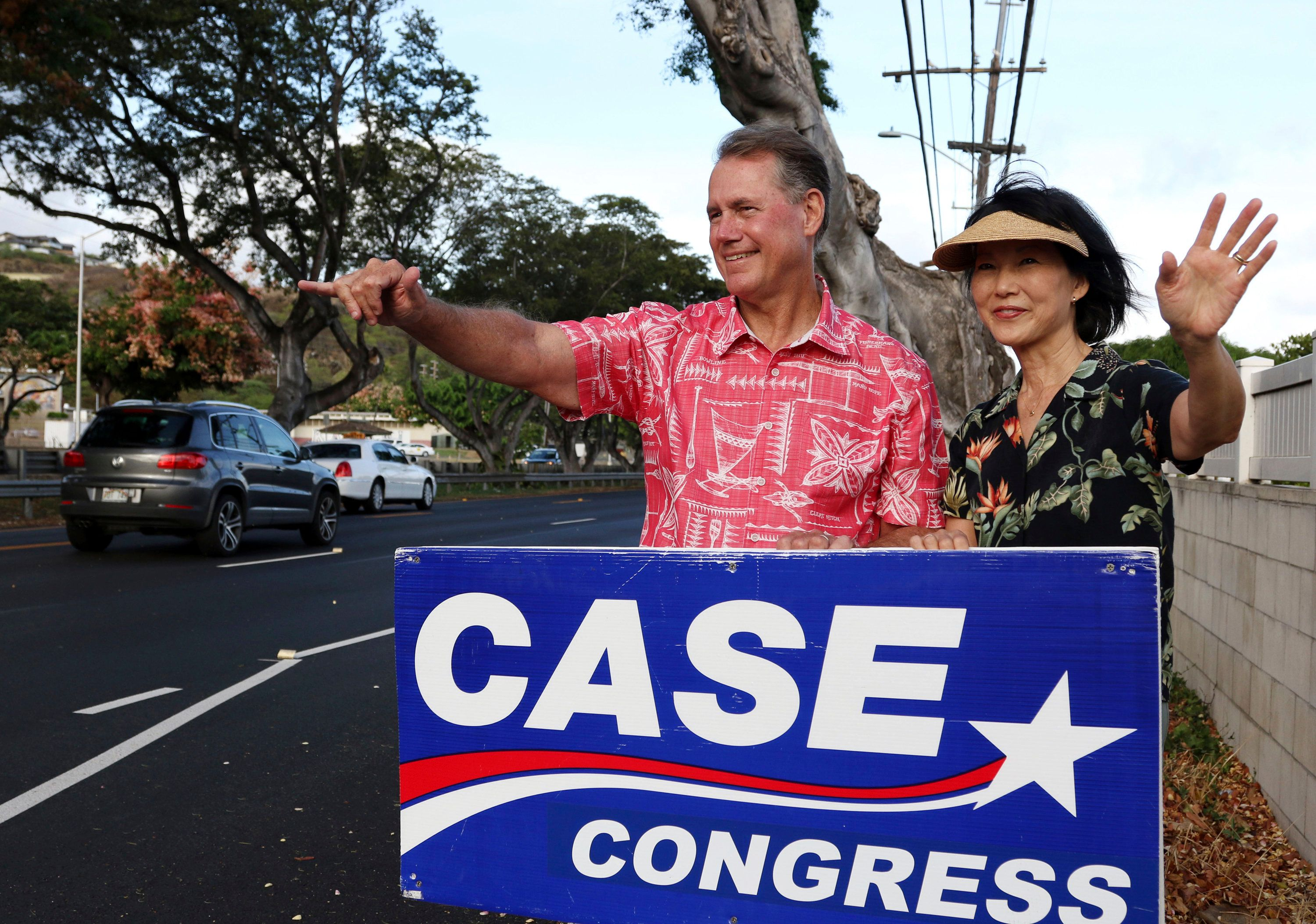 In this July 24, 2018, photo, U.S. House candidate Ed Case and his wife, Audrey Case, greet evening commuters while campaigning in Honolulu. The seat representing Honolulu in the U.S. Congress is open for anyone's taking, as incumbent U.S. Rep. Colleen Hanabusa runs for governor instead of re-election. (AP Photo/Audrey McAvoy)