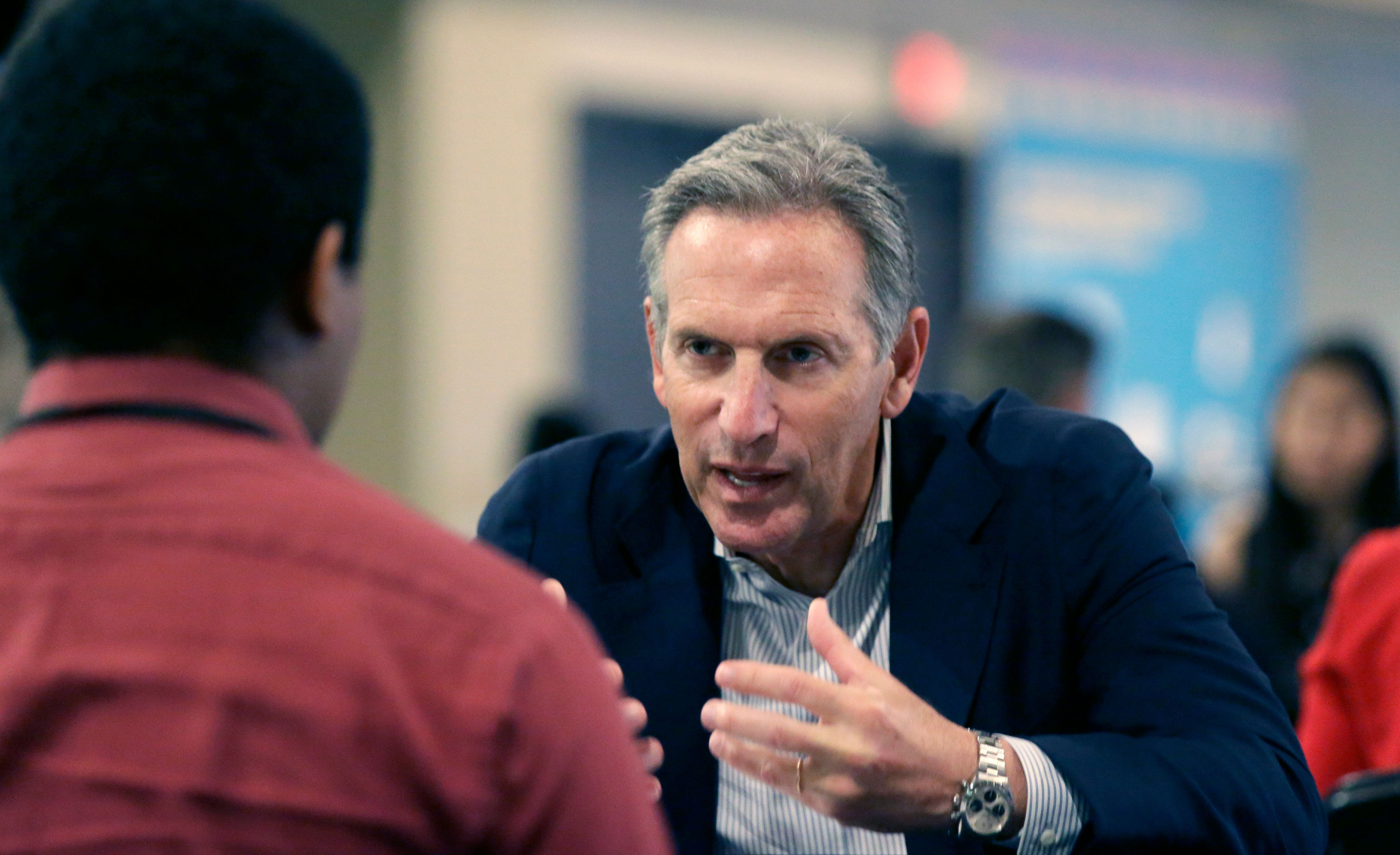 Starbucks CEO Howard Schultz, right, speaks to a job seeker during the Opportunity Fair and Forum employment event in Dallas, Friday, May 19, 2017. (AP Photo/LM Otero)