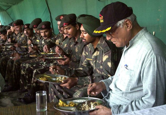 George Fernandes has a lunch with soldiers of the Indian Army at an army base in Shariefabad, north of...