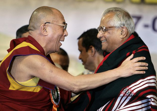 ibetan spiritual leader the Dalai Lama gestures as he felicitate former Union Defence minister George...