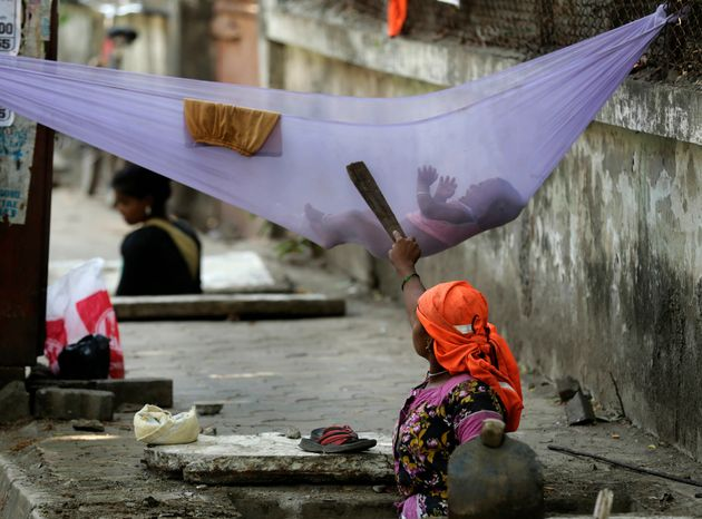 A woman labourer pacifies her child while cleaning a manhole on a sidewalk in Mumbai. The number of poor...