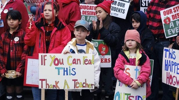 Elementary school students Capri Mac, right, and her brother Sawyer, second from right, support teachers during a citywide st