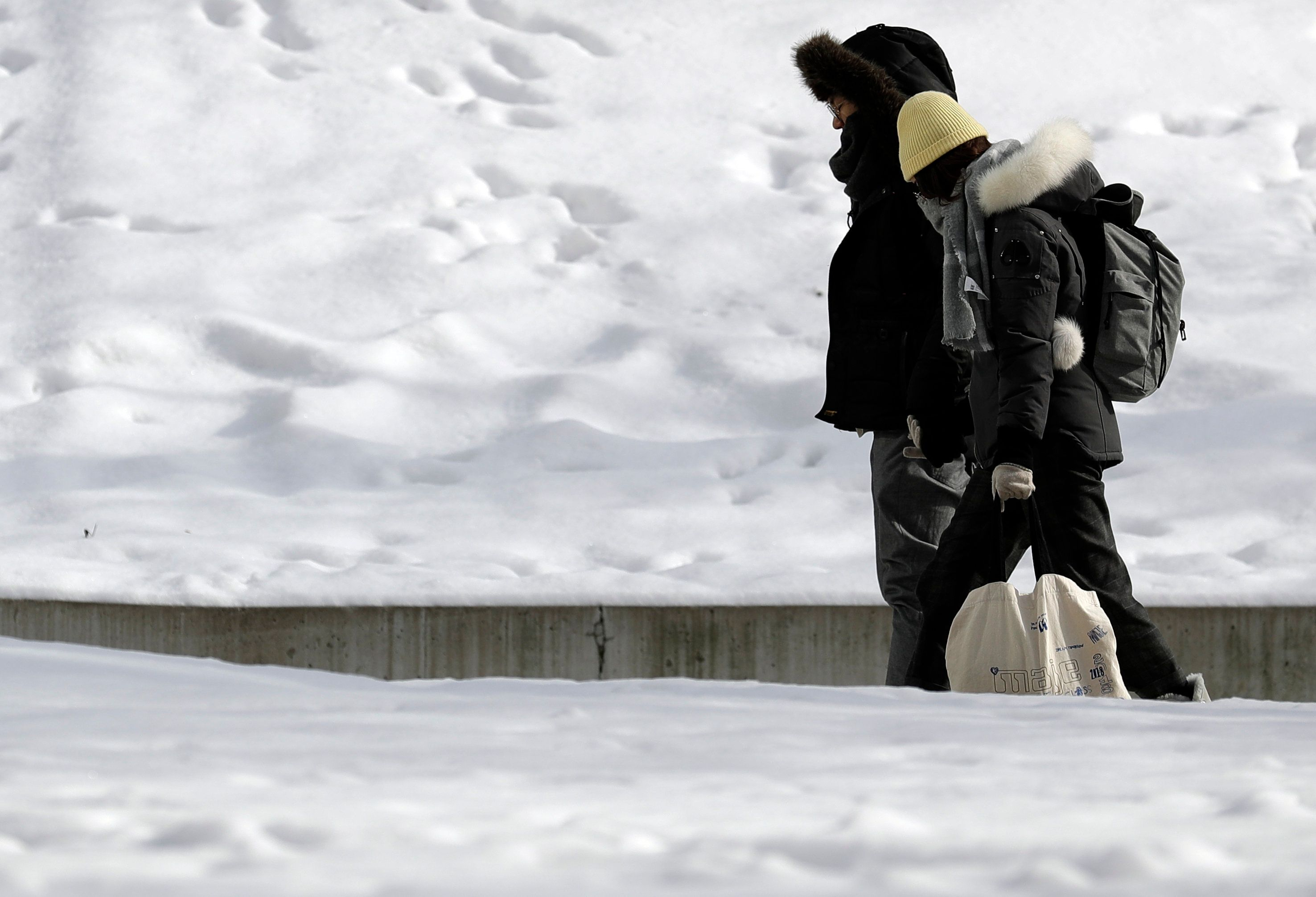 People are bundled up against Chicago's cold, in downtown Chicago, Sunday, Jan. 27, 2019. More than with many snowstorms Chicagoans have endured in recent history, where you live will greatly impact how much snow you arise to Monday morning, forecasters said. (AP Photo/Nam Y. Huh)