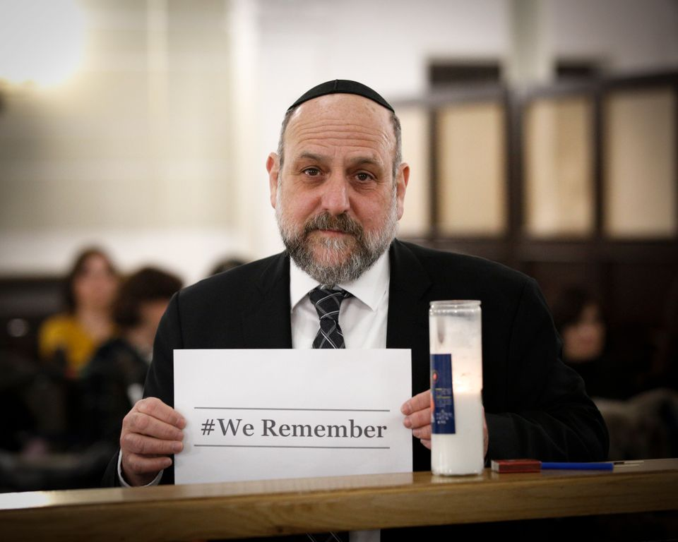Chief Rabbi of Poland Michael Shudrich holds a sign in remembrance of the viticims of the Holocaust at the Nozyk synagogue in
