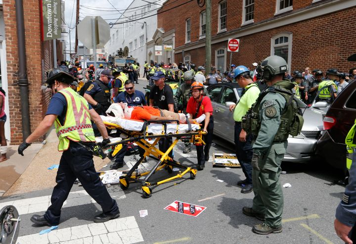 Rescue personnel help injured people after a car ran into a large group of counterprotesters at a white nationalist rally in