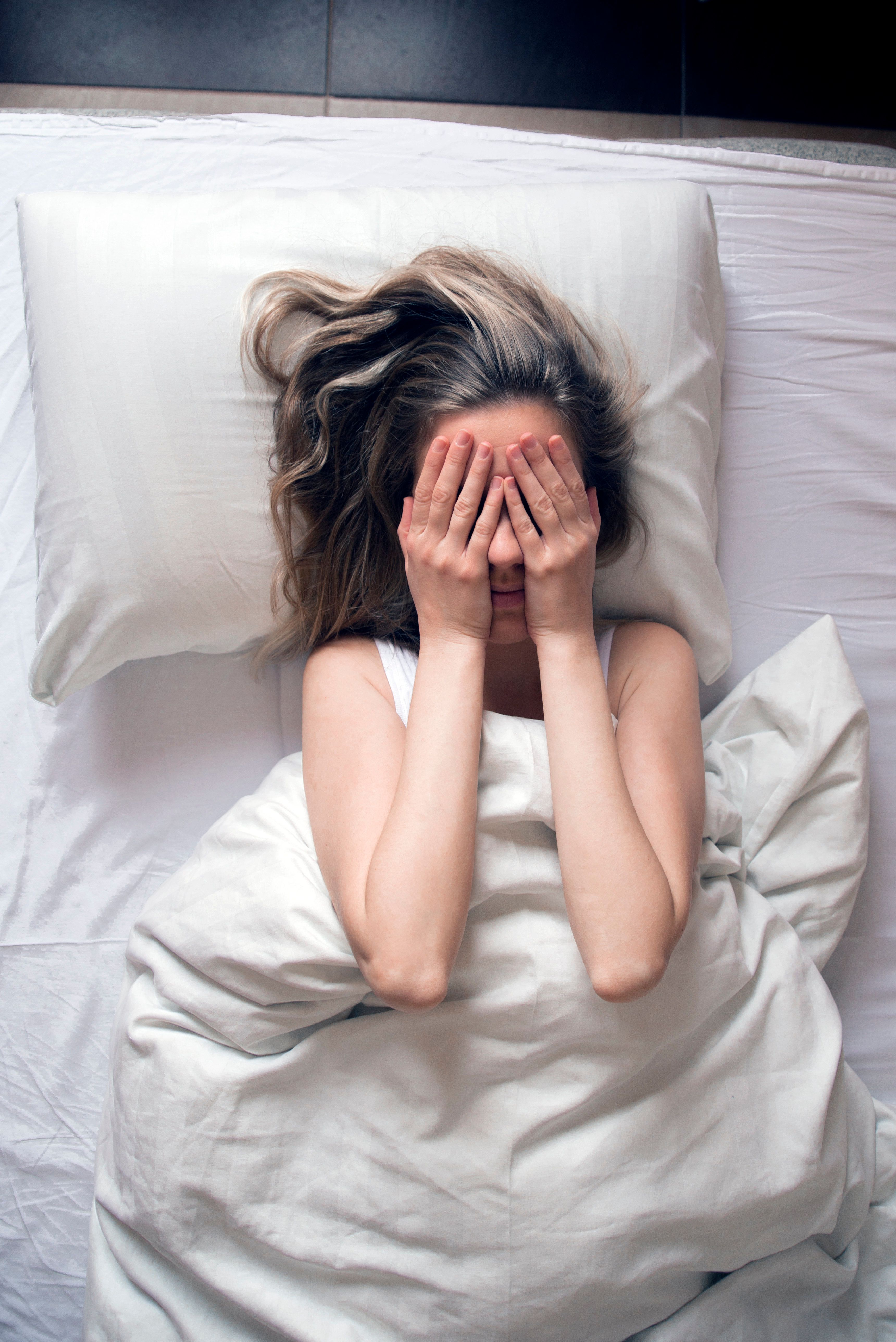 Girl long haired brunette lying on back on white bed having insomnia and covering hide face hands. Early awakened. Naughty sunny morning. top view, feeling sad or depressed