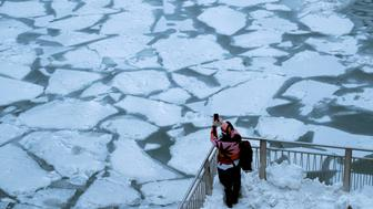 A pedestrian stops to take a photo by Chicago River, as bitter cold phenomenon called the polar vortex has descended on much of the central and eastern United States, in Chicago, Illinois, U.S., January 29, 2019.  REUTERS/Pinar Istek       TPX IMAGES OF THE DAY