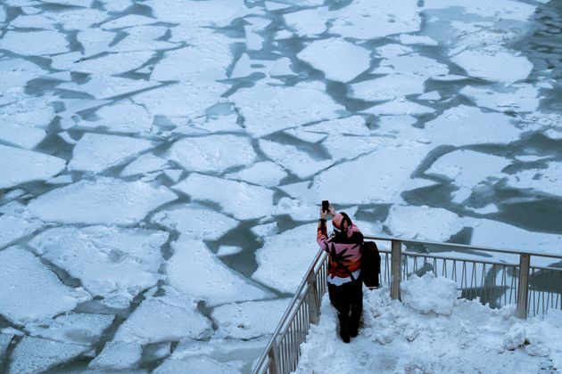 A pedestrian stops to take a photo by Chicago River, as bitter cold phenomenon called the polar vortex...
