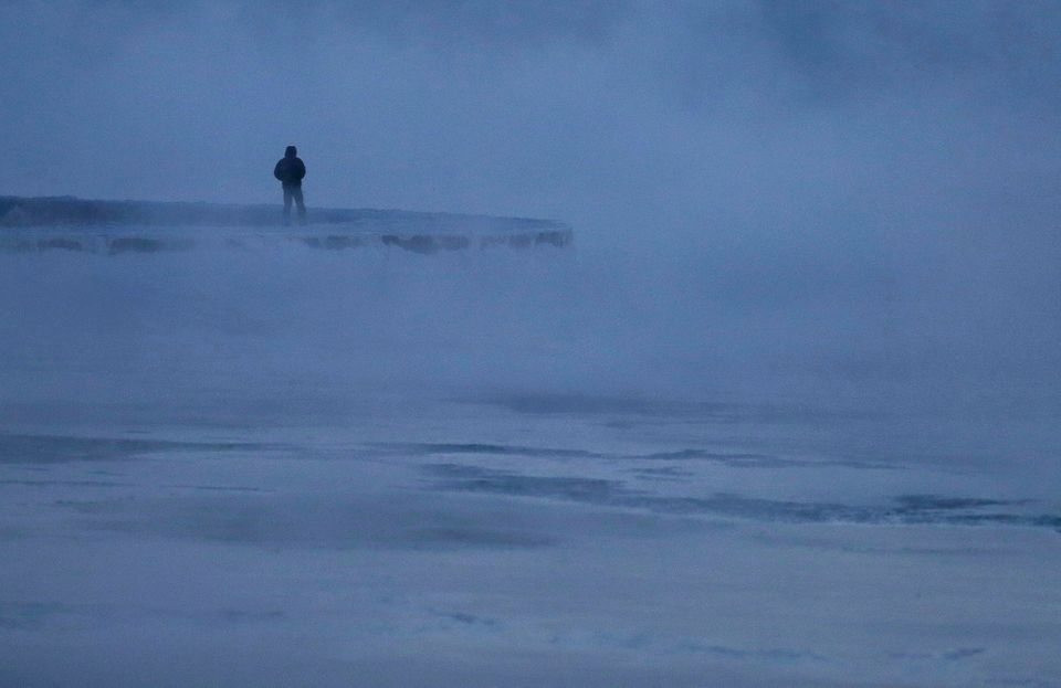 A man walks along the shore of Lake Michigan, Wednesday, Jan. 30, 2019, in Chicago.