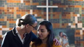 Hayarpi Tamrazyan, a 21-year-old Armenian asylum seeker, right, gets a hug from spokesperson Florine Kuethe inside the Bethel chapel in The Hague, Netherlands, Thursday, Dec. 13, 2018. For more than 6 weeks, a rotating roster of preachers and visitors has been leading a non-stop, round-the-clock service at a small Protestant chapel in a quiet residential street in The Hague in an attempt to prevent the deportation of the Tamrazyan family. (AP Photo/Peter Dejong)