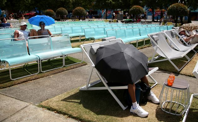 Spectators protect themselves from the heat with umbrellas as they watch tennis on a large video screen...