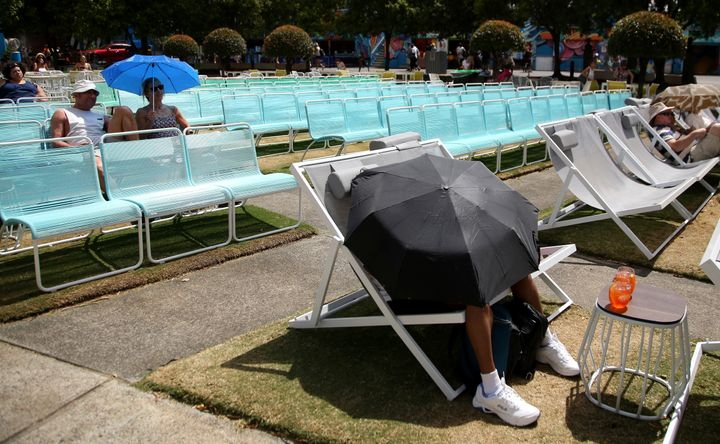 Spectators protect themselves from the heat with umbrellas as they watch tennis on a large video screen at the Australian Ope