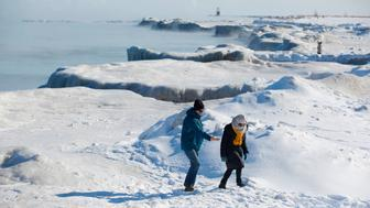 People walk along Lake Michigan's frozen shoreline as temperatures dropped to -20 degrees F (-29C) on January 30, 2019 in Chicago, Illinois. - Frostbite warnings were issued for parts of the US Midwest on January 30, 2019, as temperatures colder than Antarctica grounded flights, forced schools and businesses to close and disrupted life for tens of millions. (Photo by JOSHUA LOTT / AFP)        (Photo credit should read JOSHUA LOTT/AFP/Getty Images)