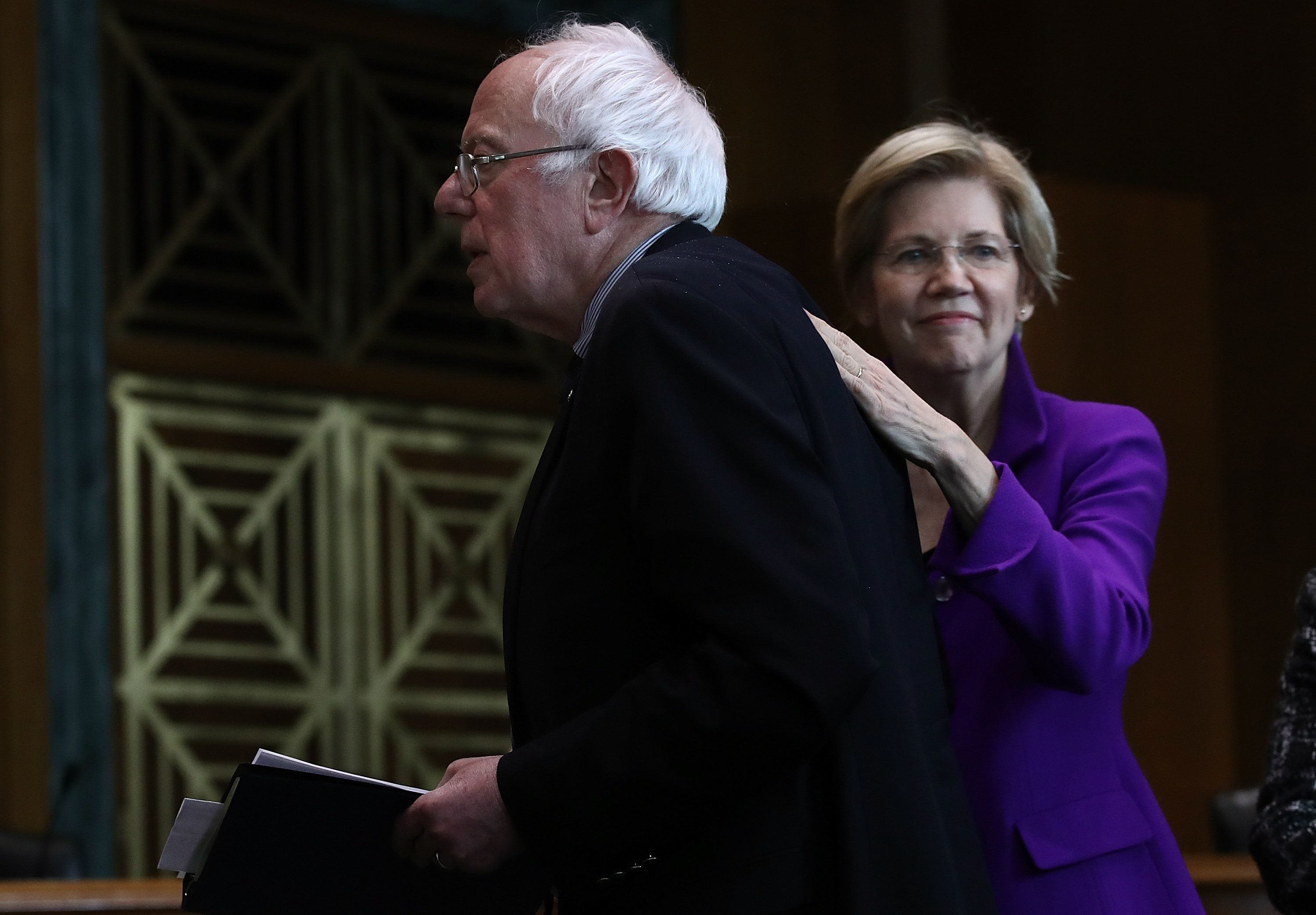 WASHINGTON, DC - FEBRUARY 16:  Sen. Elizabeth Warren (R) (D-MA) pats Sen. Bernie Sanders (L) (I-VT) on the back after Sanders spoke at a news conference on the Social Security system February 16, 2017 in Washington, DC. The news conference, hosted by Social Security Works, was held to mark 'the day that millionaires stop paying into Social Security for the rest of the year' and to 'demand that the wealthiest pay their fair share into Social Security.'  (Photo by Win McNamee/Getty Images)