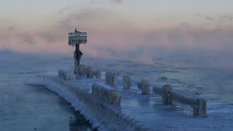 A harbor light is covered with snow and ice on the Lake Michigan at 39th Street Harbor, Wednesday, Jan. 30, 2019, in Chicago. A deadly arctic deep freeze enveloped the Midwest with record-breaking temperatures on Wednesday, triggering widespread closures of schools and businesses, and prompting the U.S. Postal Service to take the rare step of suspending mail delivery to a wide swath of the region. (AP Photo/Nam Y. Huh)