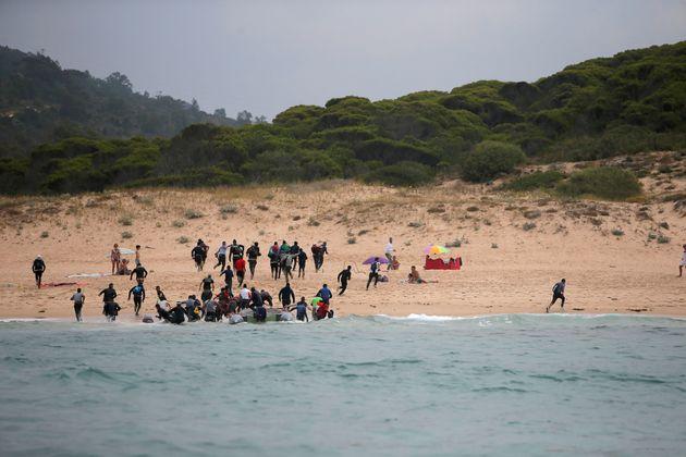 Des migrants débarquent d'un canot pneumatique sur la plage de Del Canuelo après avoir...