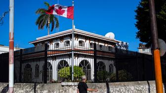 FILE - In this April 17, 2018 file photo, a  man walks beside Canada's embassy in Havana, Cuba.  Canada announced Wednesday, Jan. 30, 2019,  it is removing up to half of the Canadians at its embassy in Cuba after another diplomat was found to have fallen mysteriously ill. Canada has confirmed 14 cases of mysterious health problems since early 2017.  (AP Photo/Desmond Boylan, File)