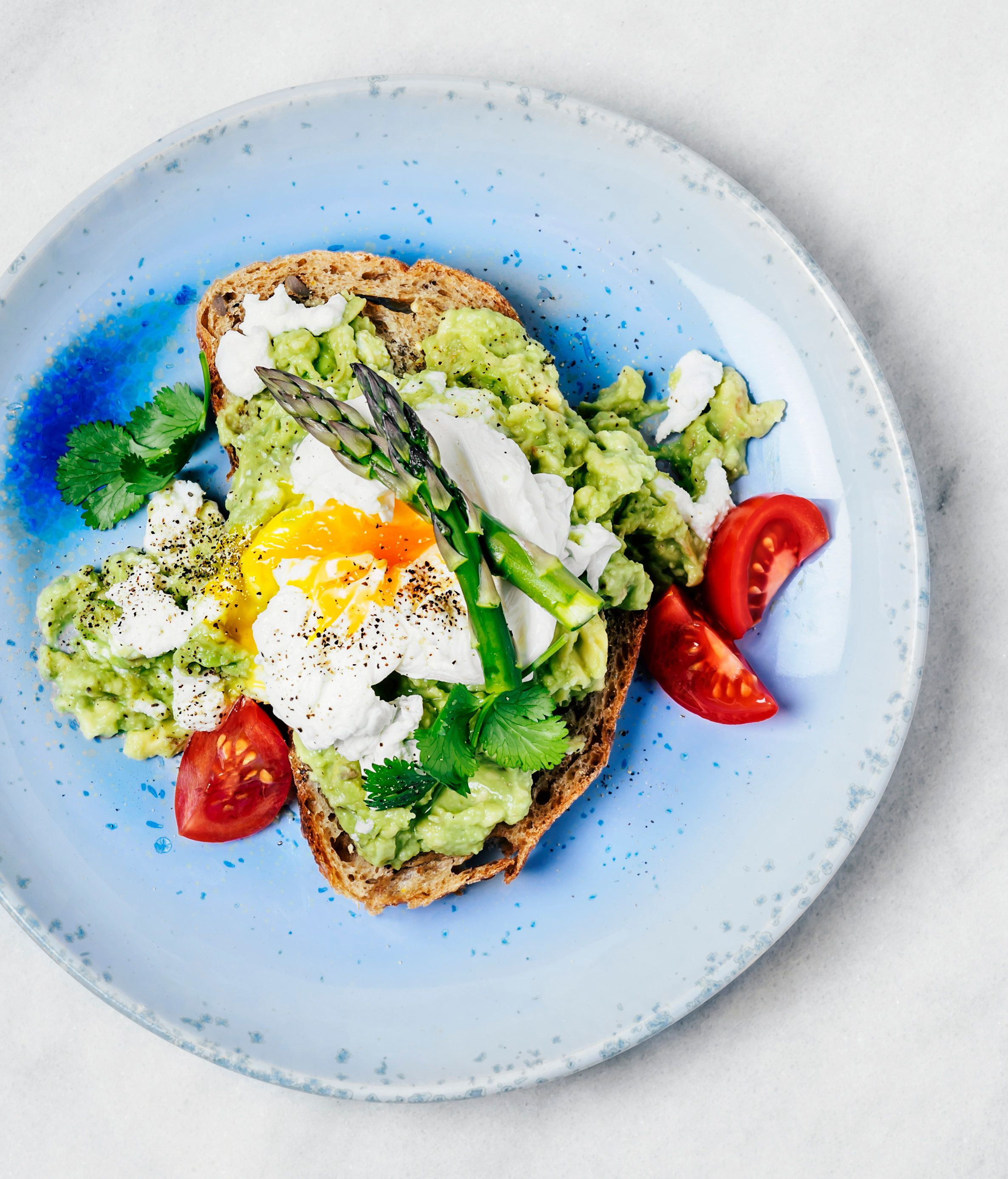 Sandwich with avocado, poached eggs, tomatoes and asparagus on a blue plate on white background