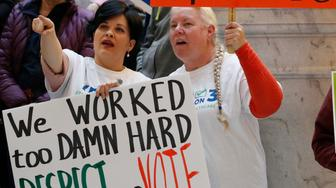 Tiffiny Malo, left, and Pam Harrison, right, supporters of a voter-approved measure to fully expand Medicaid gather others at a rally to ask lawmakers not to change the law during the first day of the Utah Legislature, at the Utah State Capitol Monday, Jan. 28, 2019, in Salt Lake City. (AP Photo/Rick Bowmer)