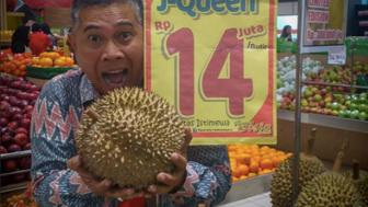 A man poses with a J-Queen durian in Jakarta, Indonesia