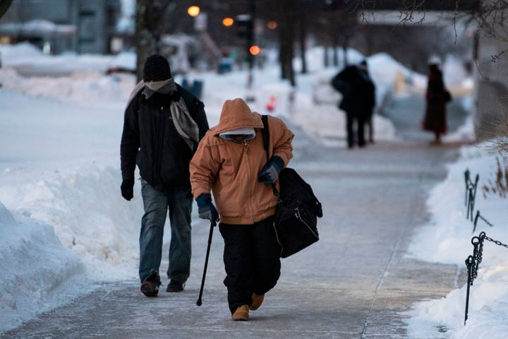 Men walk from one shelter to another in the early morning as temperatures reach -49 with wind chill in Madison, Wis. Jan. 30,