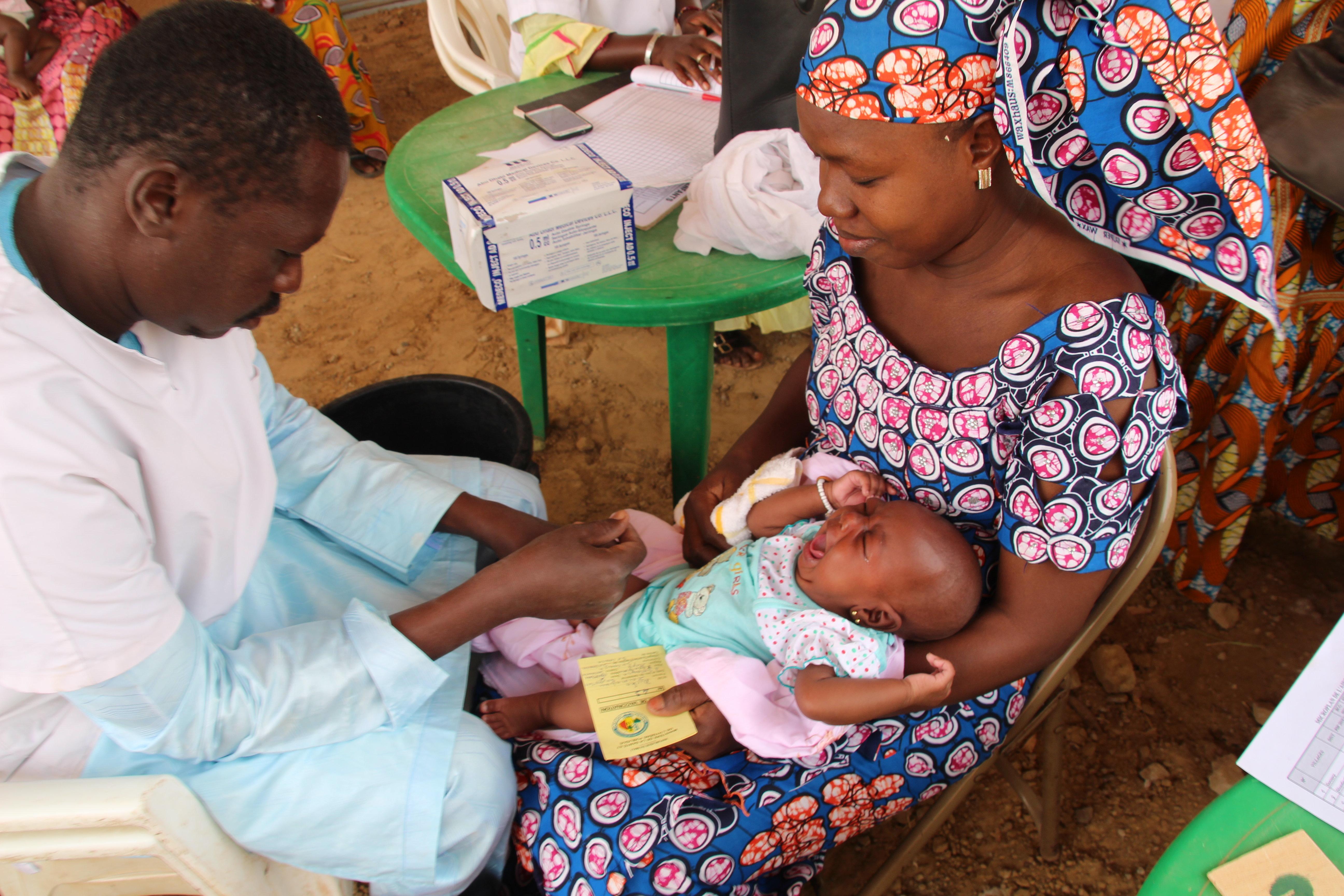 Eine junge Mutter hält ihr schreiendes Baby auf dem Schoss während ein Mitarbeiter eines Gesundheitszentrums...