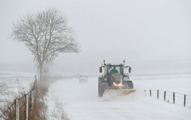 A tractor with a snowplough clears the B3081 near to Shaftesbury in Dorset on