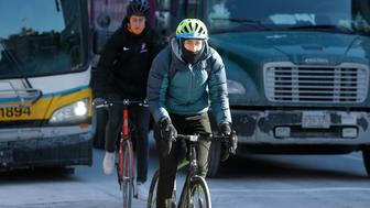 Cyclists brave freezing temperatures as they navigate traffic, Thursday, Jan. 31, 2019, in the Harvard Square neighborhood of Cambridge, Mass. Temperatures dipped into single digits in areas around the state early Thursday. (AP Photo/Steven Senne)