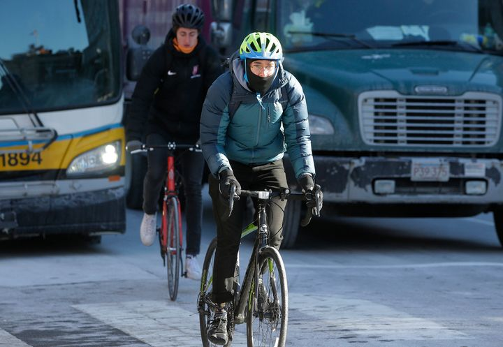 Cyclists brave freezing temperatures as they navigate traffic in Massachusetts.