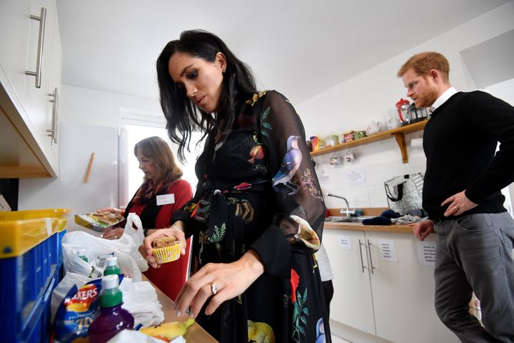 Meghan and Prince Harry in the One25 kitchen with a volunteer.