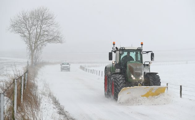 A tractor with a snow plough clears the snow on the B3081 near to Shaftesbury in Dorset
