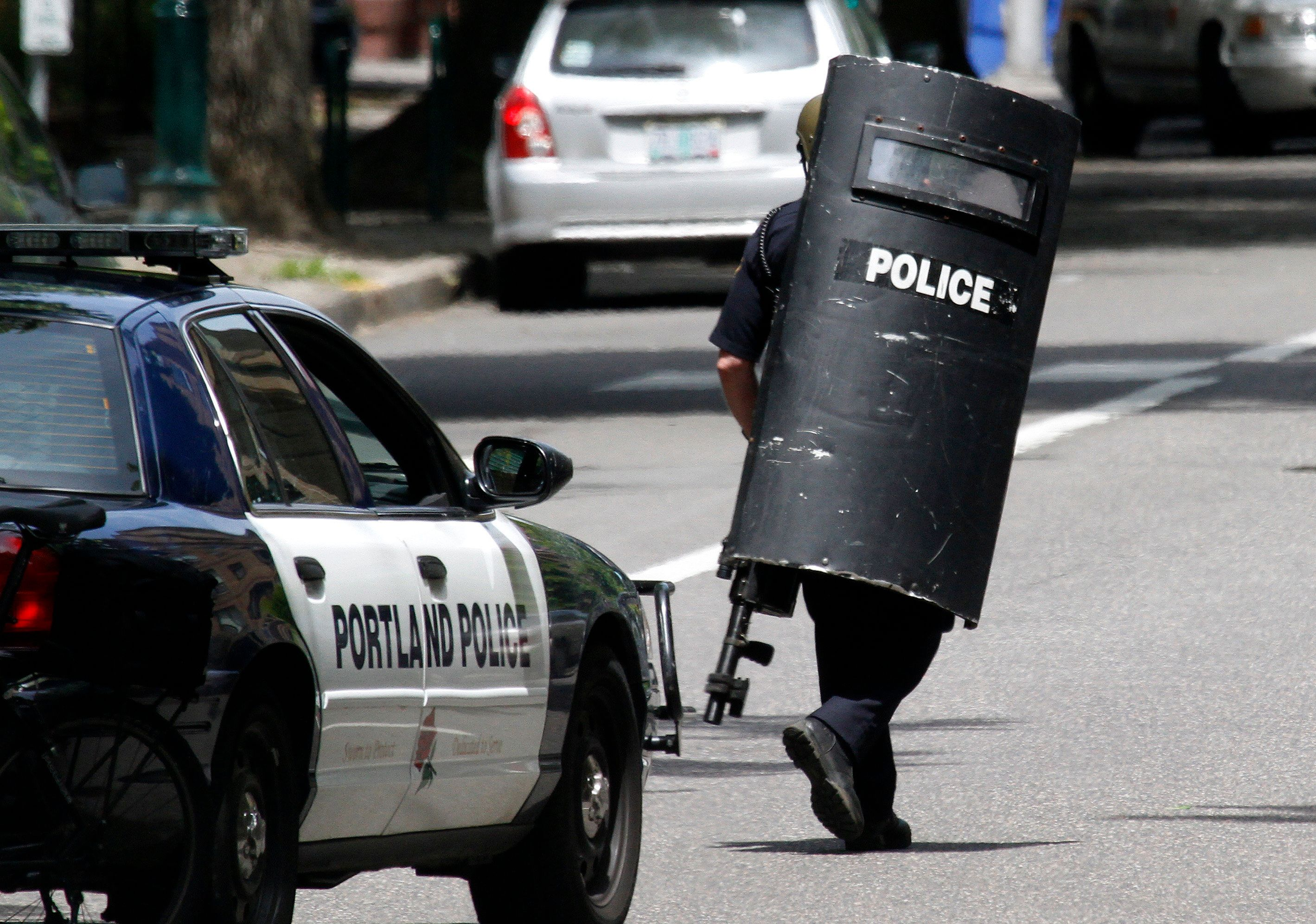 A Portland police officer heads down the street while looking for a man who is alleged to have pulled a handgun on a Portland State University security officer when the officer approached him and another man in Portland, Ore., Monday, June 11, 2012. Police cordoned off and searched a parking structure near the campus but found no gunman. (AP Photo/Don Ryan)