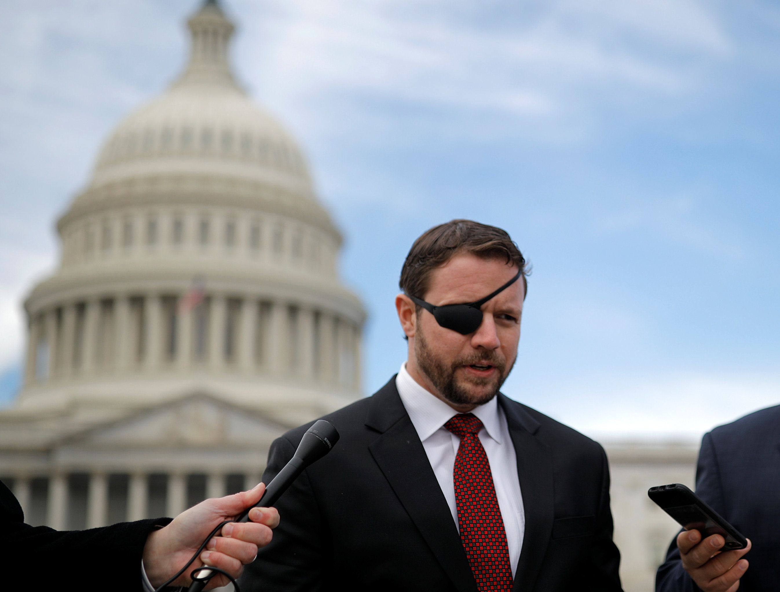 Republican Representative-elect Dan Crenshaw talks with reporters as he arrives for a class photo with incoming newly elected members of the U.S. House of Representatives on Capitol Hill in Washington, U.S., November 14, 2018. REUTERS/Kevin Lamarque