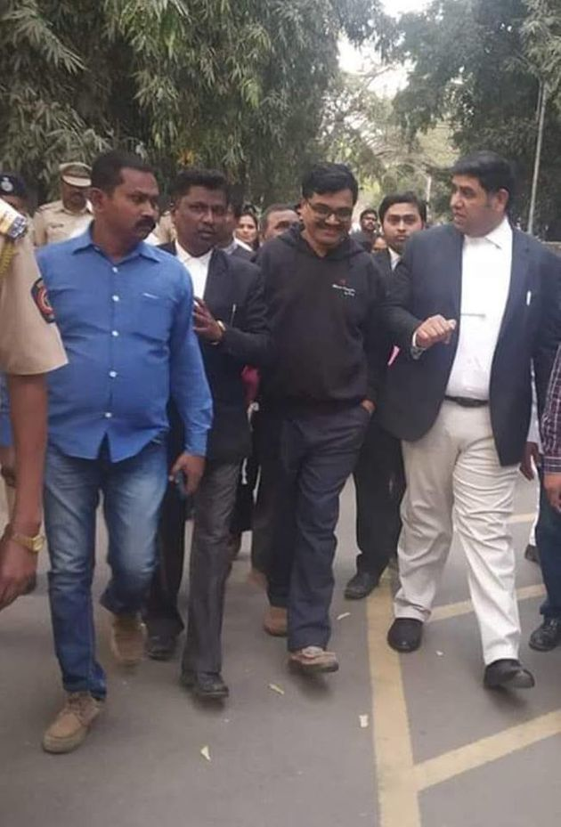 Anand Teltumbde walking out of Pune district court with his lawyer Rohan Nahar on Saturday after being