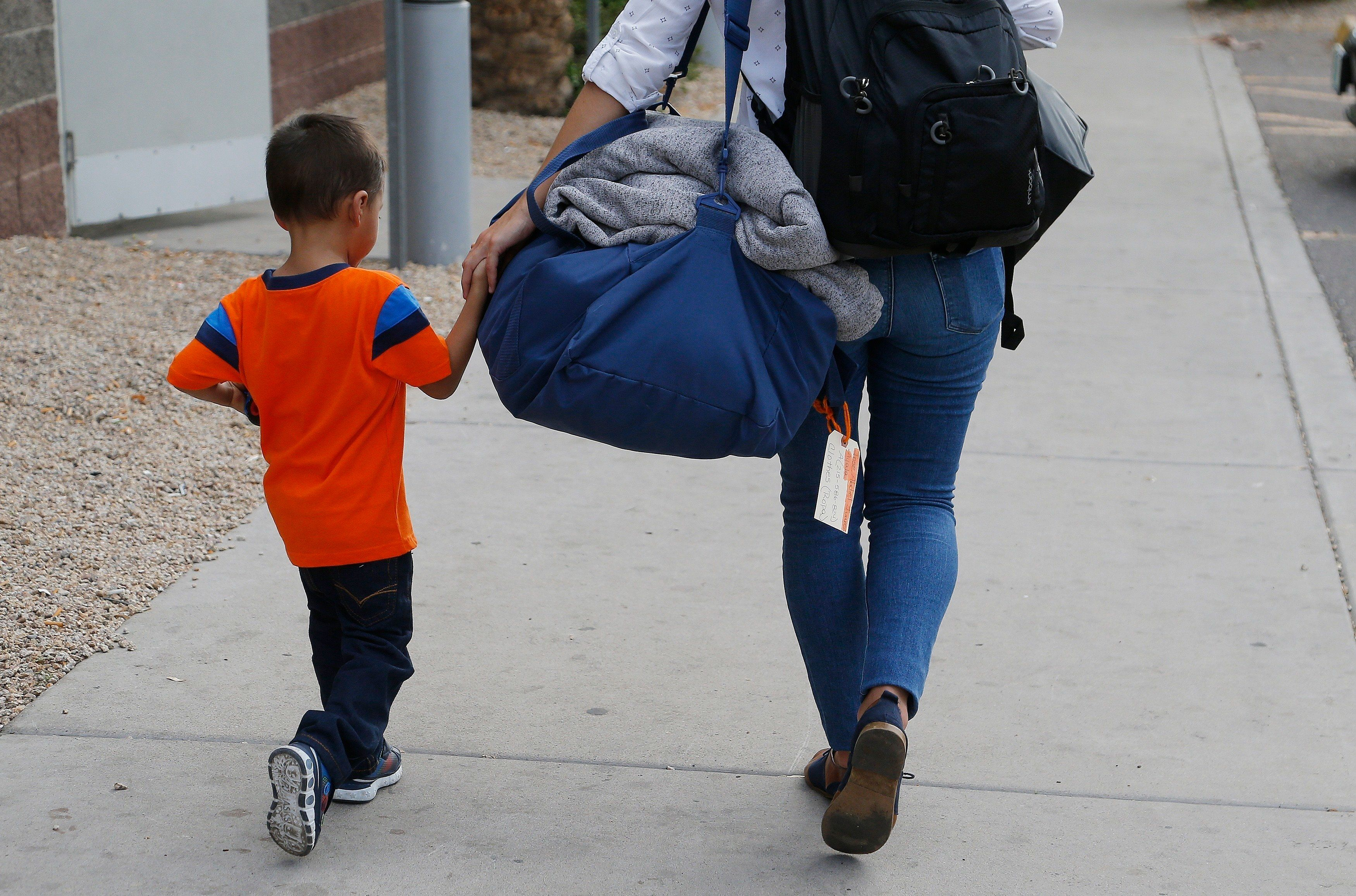 FILE - In this July 10, 2018, file photo, three-year-old Jose Jr., from Honduras, is helped by representative of the Southern Poverty Law Center as he is reunited with his father in Phoenix. The government's separation of families at the border, a consequence of a zero-tolerance policy that President Donald Trump's administration officially began in spring, drew worldwide outrage. (AP Photo/Ross D. Franklin, File)