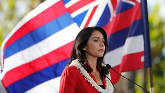 As the State of Hawaii flag flies in the background, U.S. Rep. Tulsi Gabbard, D-Hawaii, speaks during a campaign rally announcing her candidacy for president in Waikiki, Saturday, Feb. 2, 2019, in Honolulu. (AP Photo/Marco Garcia)