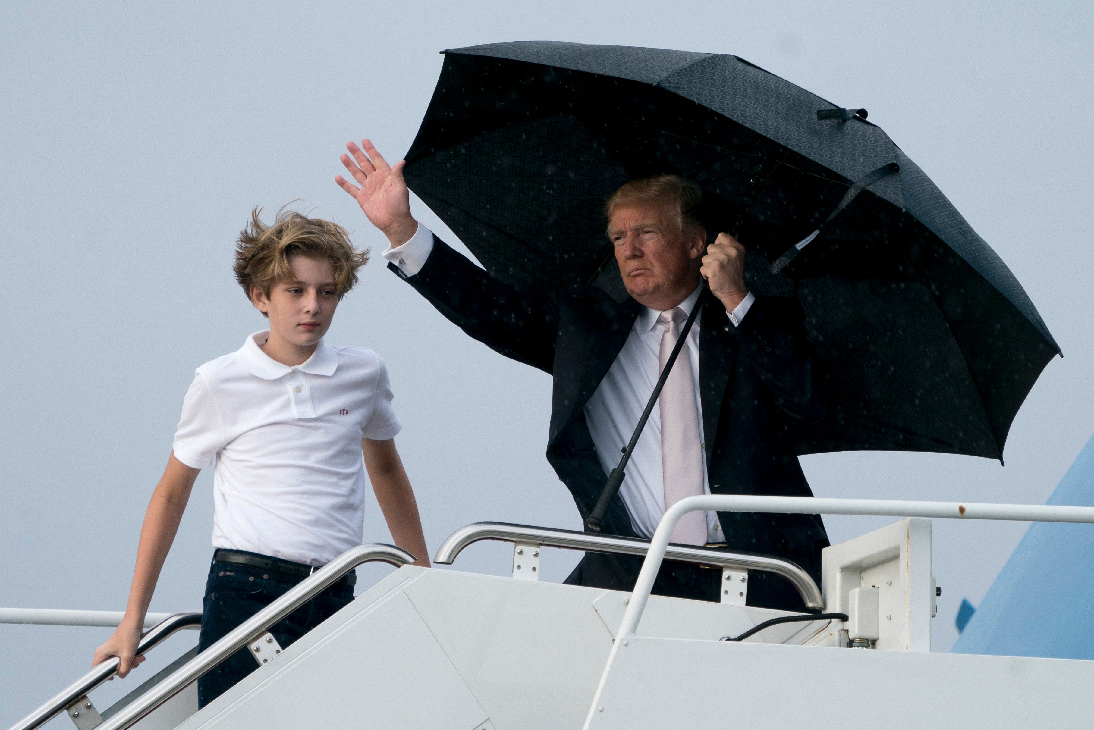 President Donald Trump and his son Barron board Air Force One at Palm Beach International Airport in West Palm Beach, Fla., Monday, Jan. 15, 2018, to travel to Washington. President Trump spent the holiday weekend at Mar-a-Lago, his club in Palm Beach, Fla. (AP Photo/Andrew Harnik)