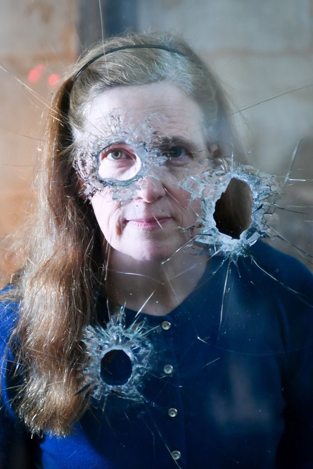 Salisbury Cathedral archivist Emily Naish looks through holes in reinforced glass that were left after...