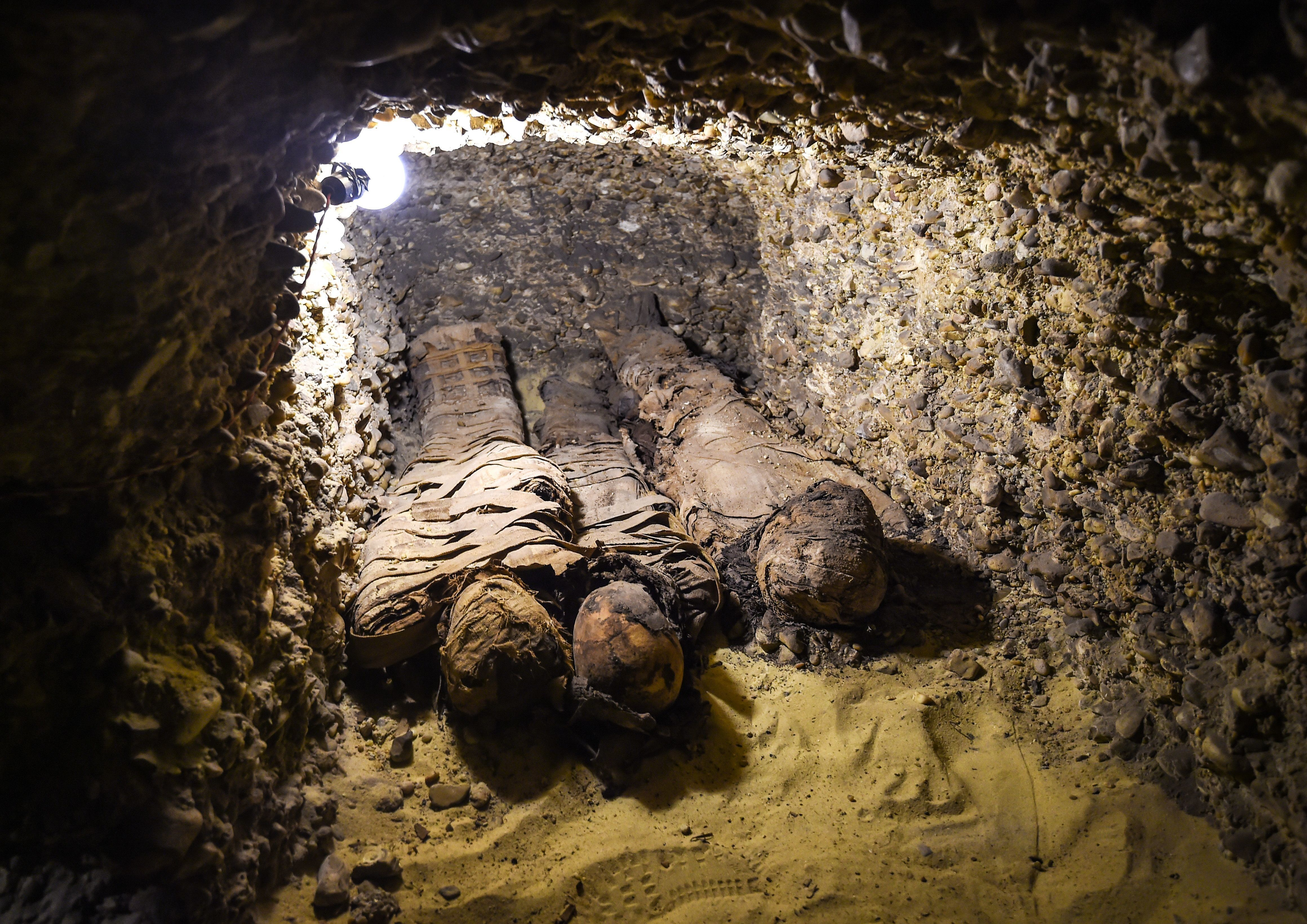 This picture taken on February 2, 2019 shows newly-discovered mummies wrapped in linen found in burial chambers dating to the Ptolemaic era (323-30 BC) at the necropolis of Tuna el-Gebel in Egypt's southern Minya province, about 340 kilometres south of the capital Cairo. - Egypt's Antiquities Minister said on February 2 that a joint mission from the ministry and Minya University's Archaeological Studies Research Centre found upon a collection of Ptolemaic burial chambers engraved in rock and filled with a large number of mummies of different sizes and genders. The minister added that the newly discovered tombs may be a familial grave for a family from the elite middle class. (Photo by MOHAMED EL-SHAHED / AFP)        (Photo credit should read MOHAMED EL-SHAHED/AFP/Getty Images)