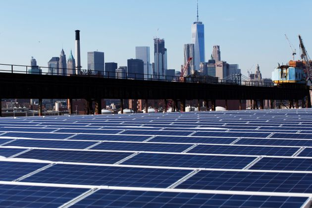 The Manhattan skyline peers over a rooftop covered with solar panels at the Brooklyn Navy Yard in New