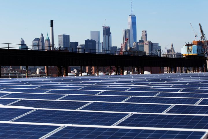 The Manhattan skyline peers over a rooftop covered with solar panels at the Brooklyn Navy Yard in New York.