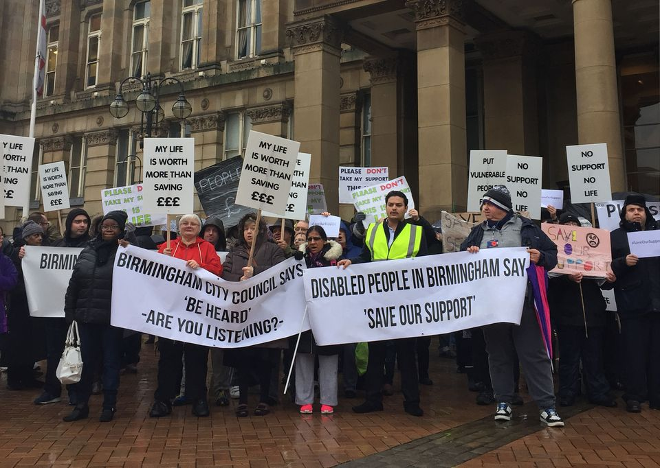 Protestors in Birmingham wave placards objecting to cuts to council