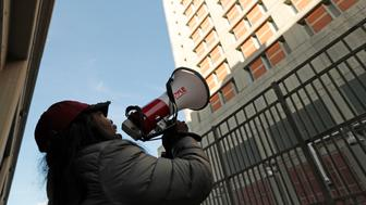 Catana Yehudah, of the Bronx, uses a megaphone to speak to prisoners from outside the Metropolitan Detention Center, a federal prison of all security levels, where prisoners haven't had access to heat, hot water, electricity and sanitary conditions since earlier in the week, including through the recent frigid weather, Sunday, Feb. 3, 2019, in the Brooklyn borough of New York. Yehudah has a brother who is serving an 18-month sentence for gun possession. (AP Photo/Kathy Willens)