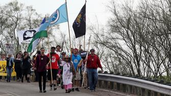 Members of the Carrizo/Comecrudo Tribe along with other opponents of wall construction convene near the river and made their way about 3 miles down to the National Butterfly Center to march in protest on Monday, Feb. 4, 2019 in Mission, Texas. (Delcia Lopez//The Monitor via AP)