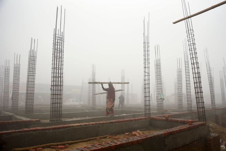 A woman carries building materials at a construction site in the morning smog near New Delhi, India.