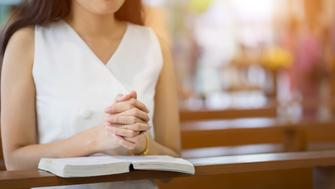 Woman hands praying on a holy bible in church for faith concept, Spirituality and Christian religion.